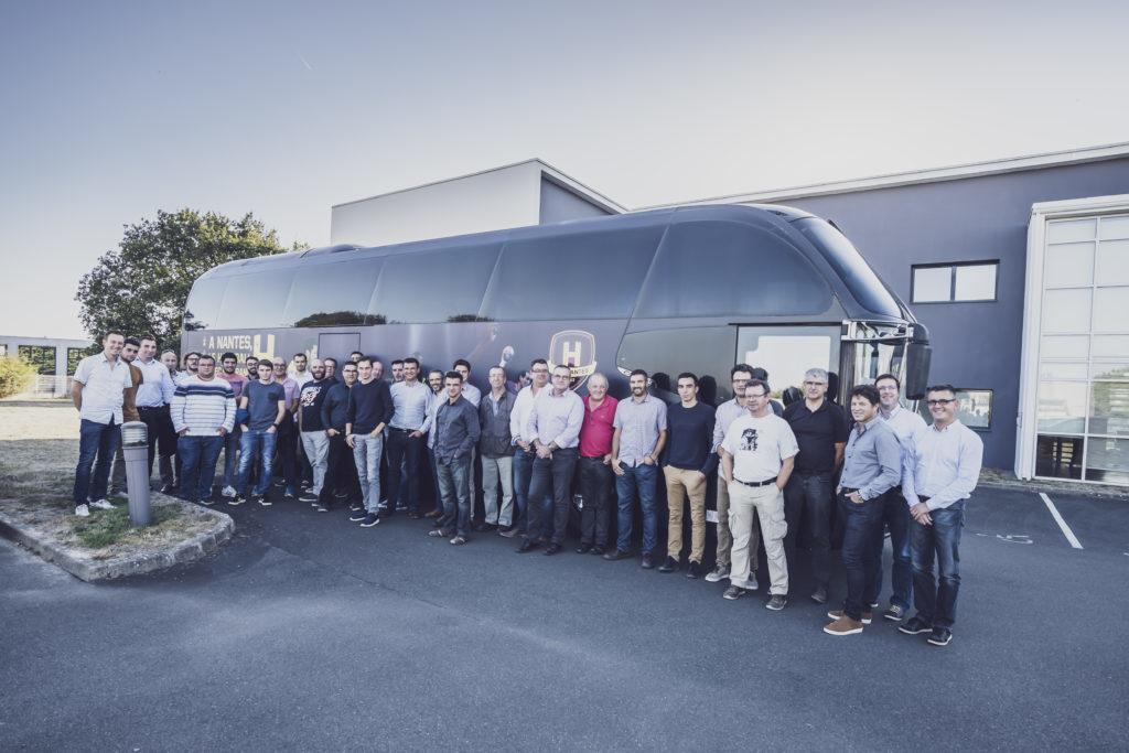 Les partenaires de l'entreprise Sofinther devant le bus officiel de l'équipe.