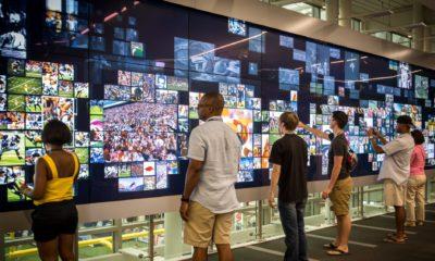 Des visiteurs interagissent avec l'écran tactile géant du College Football Hall of Fame
