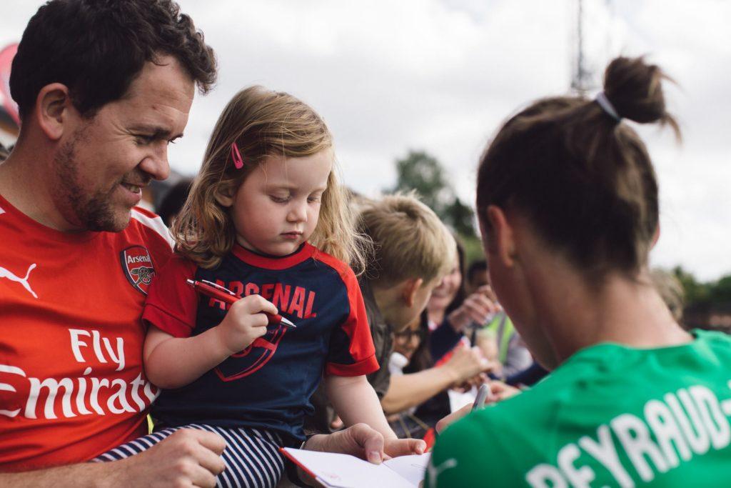 Pauline qui signe quelques autographes à des fans d'Arsenal FC