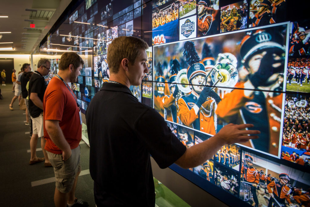Des visiteurs interagissent avec l'écran tactile géant du College Football Hall of Fame