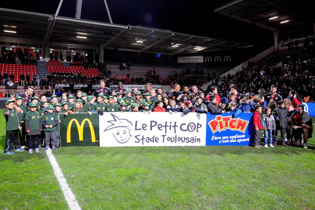 Les enfants du Petit Cop qui posent avec les joueurs au stade Ernest Wallon